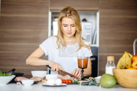 Photo for Woman slicing meat preparing meat kebab on a kitchen table with a big Chef knife. Attractive cook cutting meat on table prepares to surprise her boyfriend with delicious dish. - Royalty Free Image
