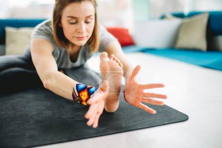 Yogi girl practicing Head-to-Knee Forward Bend Pose.