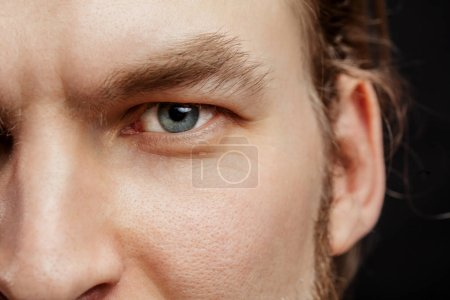 close up cropped photo of man bearded face with beautiful blue eyes