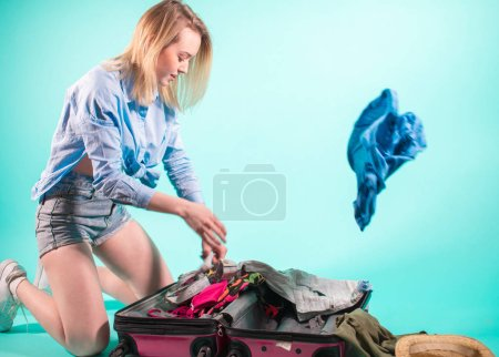 Packing clothes., young blond woman choosing necessary things for the trip .