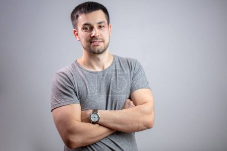 Photo for Portrait of young strong man with crossed arms.bodyguard in casual outfit. copy space. isolated grey background. confident muscular man - Royalty Free Image