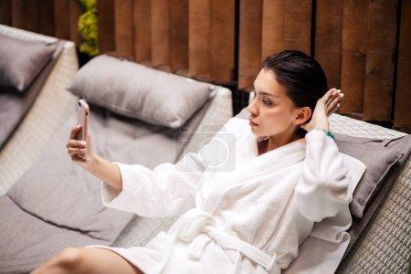 Young beauitiful woman wearing white bathrobe lying on the loung