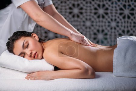 female doing massage for black haired Asian woman having problems with back