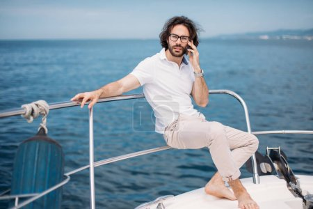 Photo pour Jeune homme d'affaires barbu parlant sur smartphone sur un yacht de luxe, profitant d'une vue magnifique sur la mer. Voile. Yachts de luxe. Concept de voyage en mer . - image libre de droit