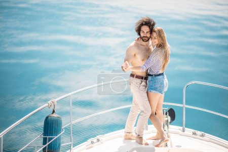 Passionate lovers dancing on bow of deck while sailing on yacht.