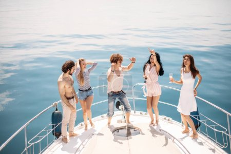 Photo for Caucasian happy friends drinking wine, dancing at exclusive boat party. Yachting in summer vacation. Cruise, Travel, vacation and youth lifestyle concept. Sea background with copyspace. - Royalty Free Image