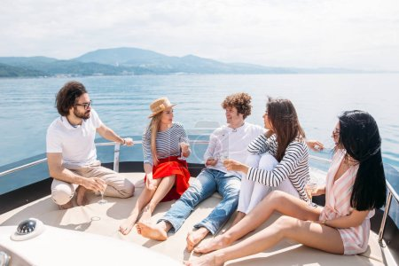 Friends having fun sailing on a yacht in sea, laughing, chatting and chilling