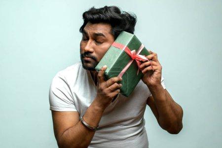 Photo pour Fermer la photo. sentimental fort indien gars essayant d'imaginer ce qu'il a été présenté. les yeux fermés. esprit de vacances - image libre de droit