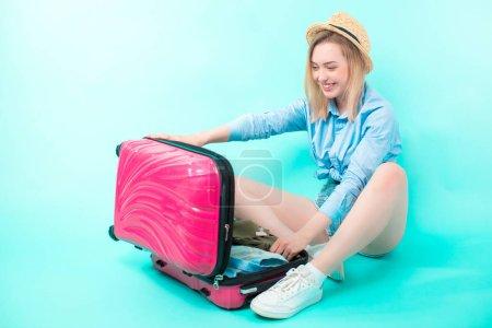 Photo pour Jeune femme ouvrant sa valise après les vacances. touriste bloque tout dans les bagages - image libre de droit