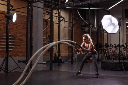 serious awesome blond girl is concentrated on the exercise with battle ropes