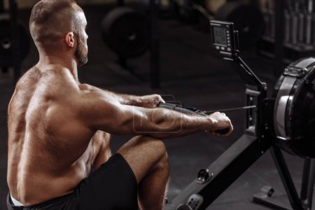 side view photo of shirtles man using th rowing machine while training