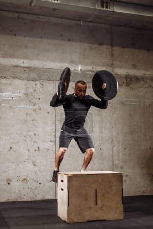 strong athlete jumping with weight plates on the box