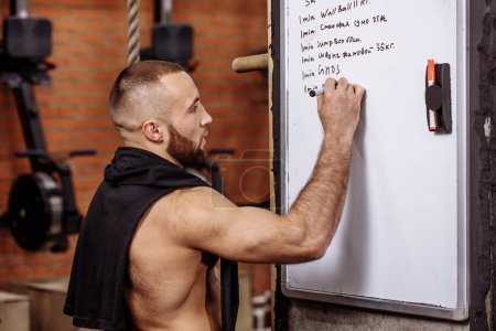 muscular fit guy is writing his training program on the board