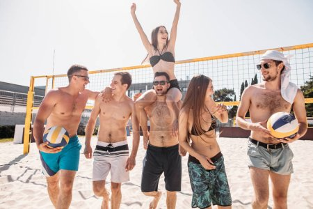 Group of young happy friends walking on beach volleyball court after game won.