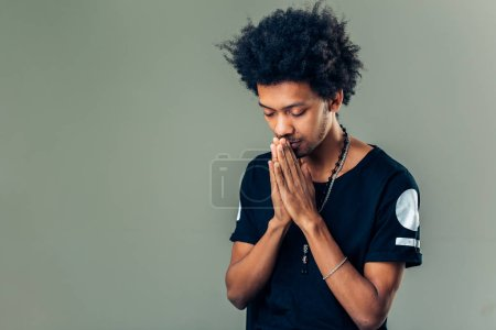 Praying african american man hoping for better. Asking God for good luck