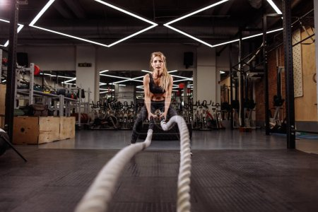 fit gorgeouse woman is working out with battle ropes to keep fit