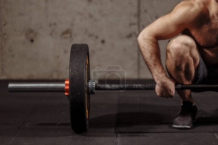 Photo for Athletic shirtless young man doing exercise with barbell in gym.close up cropped photo. focus on the barbell plate - Royalty Free Image