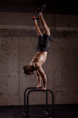 well-built gymnast performing on parallel bars
