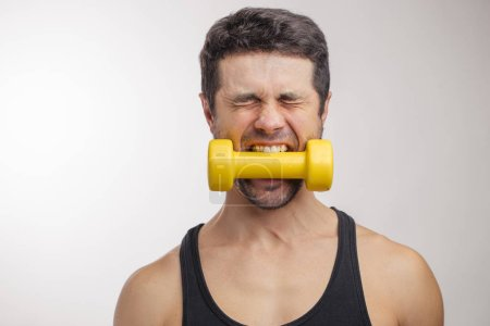 mad guy with a dumbbell clenched in his teeth