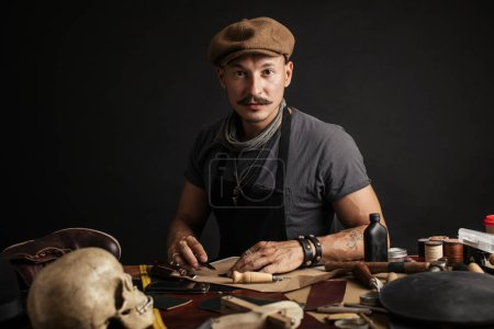 Photo for Portrait of handsome Leather goods craftsman in stylish hat doing handbags and leather accessories for ladies in his workshop on black dark background. Small business concept photo. - Royalty Free Image