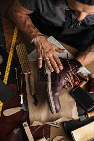 Gros plan des mains de fabricant de chaussure produisant des bottes dans son atelier de cuir