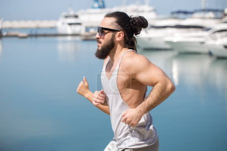 Athlete running man - male runner by the sea pier with yachts