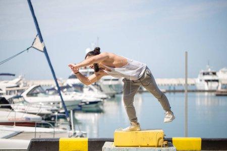 Fitness athlete doing jump squats on makeshift plyo-box on summer sea pier