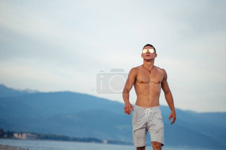 Masculine body man in sunglasses at beach with mountauns on background