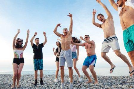 Photo pour Groupe d'amis ayant parti sur la plage, danse, saut et amusant - image libre de droit