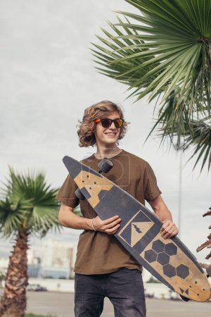 Stylish man stands on street and hold long board in hands