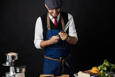 Photo for Portrait of chef cook in elegant uniform wearing cap and apron sharpens knife at the restaurant kitchen table over yellow background. Small business, Service and Catering Concept - Royalty Free Image