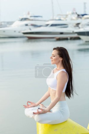 Young sportive woman is sitting on sea, marina pier and looking at horizon