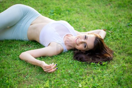 Young caucasian woman being happy to spend weekends in nature outdoors, looking at camera, relaxing on grass in countryside. View from above. Freedom concept. Calmness and relax, Human happiness.