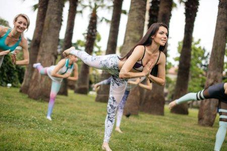 Photo pour Session Pilates en plein air, programme de loisirs d'été pour les résidents des hôtels de luxe. Groupe de femmes caucasiennes en vêtements de sport travaillant à l'extérieur le matin d'été . - image libre de droit