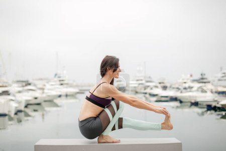 Photo for Yoga training and meditation. Fitness woman stretching legs on stone deck with sea view. - Royalty Free Image