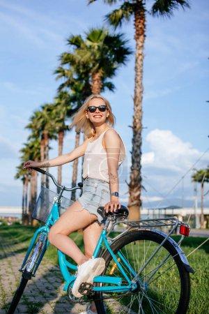 Joyful blonde woman riding bicycle in park having fun on summer afternoon
