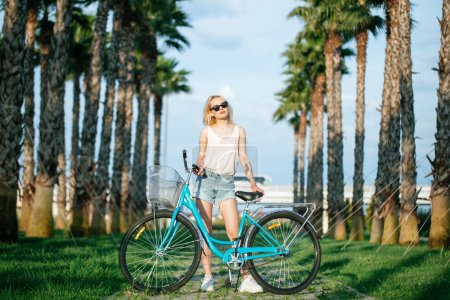 woman standing near rented bicycle in park. Summer and lifestyle