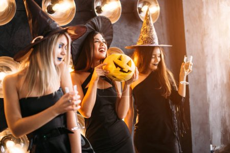 Photo for Three cheerful young women in witch halloween costumes with pumpkin - Royalty Free Image