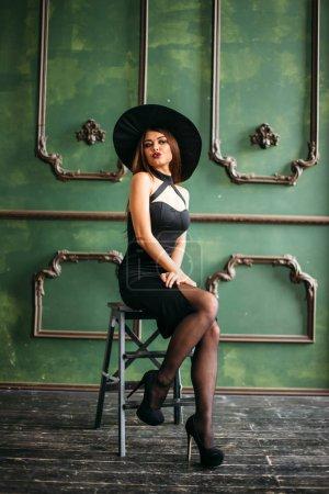Photo pour Belle jeune femme en costume noir de sorcière avec chapeau - image libre de droit