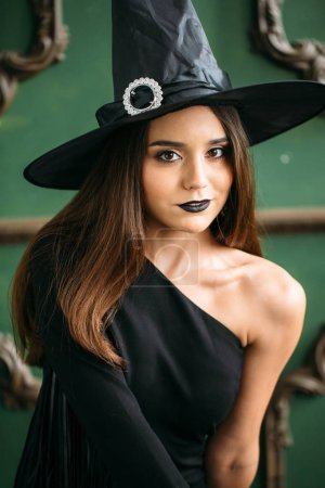 Photo for Beautiful young woman in black witch costume with hat - Royalty Free Image