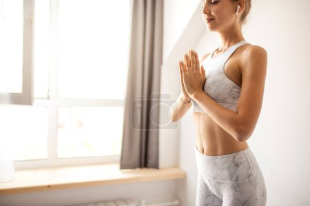 Photo for Female yoga teacher greets at the begining of practicing yoga exercise, namaste, working out, wearing sportswear, white t-shirt, leggings, studio isolated shot against window - Royalty Free Image