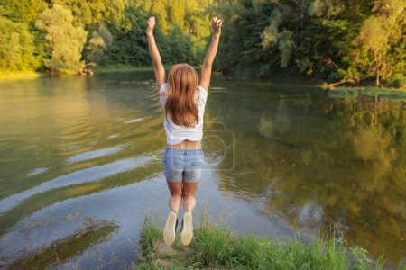 Beautiful red-haired girl enjoying nature. carefree Happy Woman.