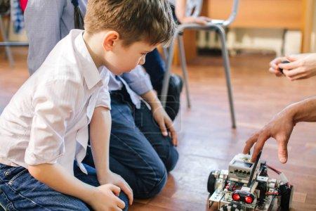 Little boy in robotics school makes robot