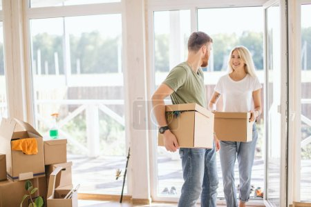 Happy Couple Carrying Cardboard Boxes Into New Home On Moving Day