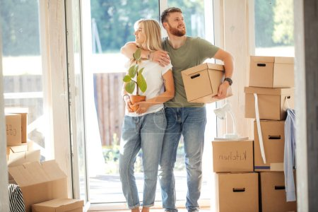 Photo for Happy smiling couple moving in new house and carrying carton boxes - Royalty Free Image