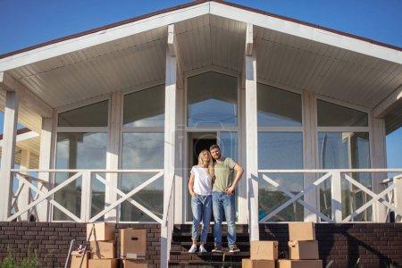 Photo pour Couple Debout sur les marches de la nouvelle maison avec des boîtes en carton mobiles - image libre de droit