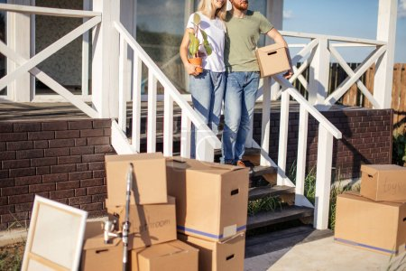 Husband and wife standing in front of new buying home with boxes