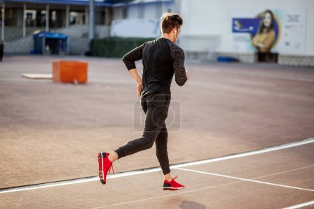 Photo for Athlete Man in black clothes running on track on sunny day - Royalty Free Image