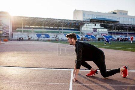 athlete on starting position at running track. Runner practicing run in stadium racetrack