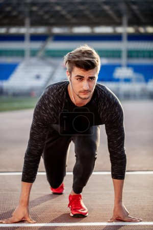 Photo for Young muscular athlete at start position on race track in stadium - Royalty Free Image